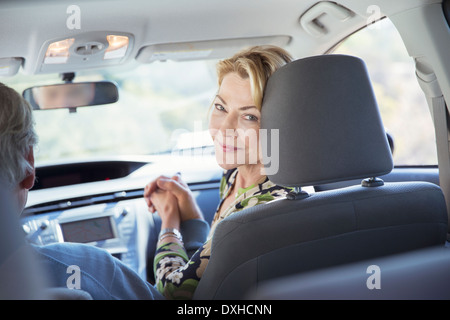 Portrait of smiling woman inside car - Stock Photo