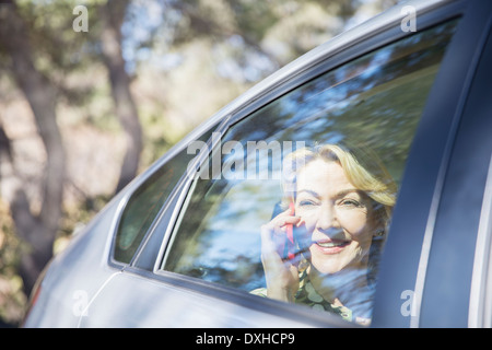 Senior woman talking on cell phone in car - Stock Photo