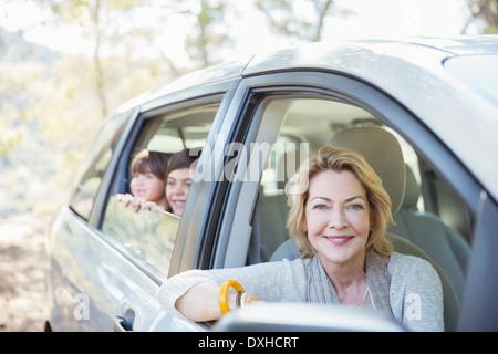 Portrait of happy grandmother and grandchildren at car windows - Stock Photo