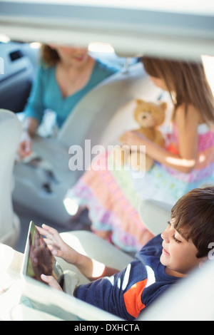 Boy using digital tablet in back seat of car - Stock Photo