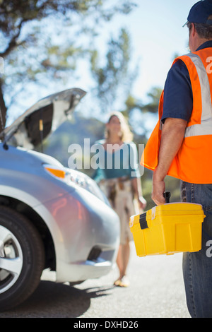 Roadside mechanic arriving to help woman - Stock Photo
