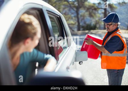 Woman watching roadside mechanic fill gas tank - Stock Photo