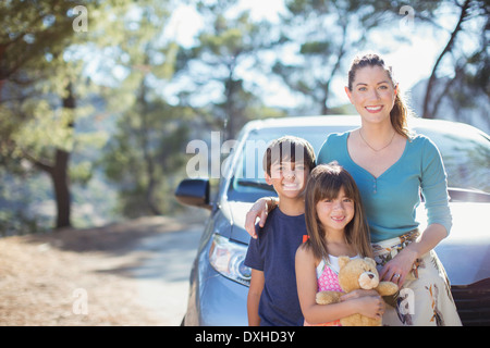 Portrait of happy family leaning on car - Stock Photo