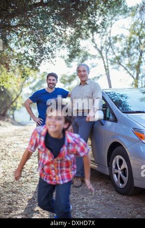 Happy multi-generation men outside car - Stock Photo