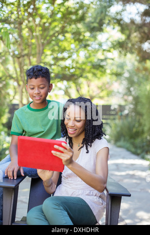 Mother and son using digital tablet outdoors - Stock Photo
