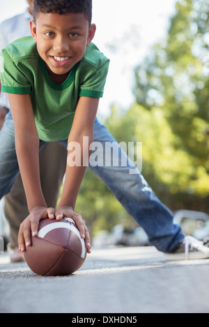 Portrait of smiling boy preparing to snap football - Stock Photo