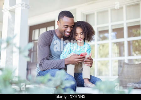 Father and daughter using cell phone on porch - Stock Photo