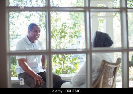 Happy senior couple talking on porch - Stock Photo