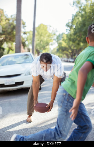 Grandfather and grandson playing football in street - Stock Photo