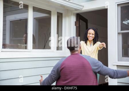 Enthusiastic woman greeting man in doorway - Stock Photo