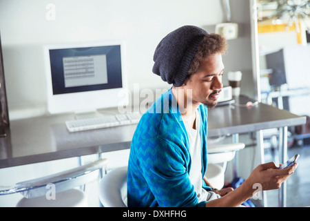 Casual businessman text messaging with cell phone in office - Stock Photo