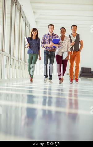 Portrait of creative business people walking in sunny corridor - Stock Photo