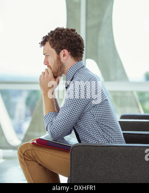 Pensive businessman sitting in office lobby - Stock Photo