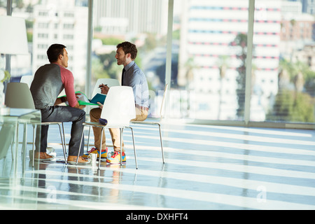 Creative businessmen meeting at circle of chairs in sunny office - Stock Photo