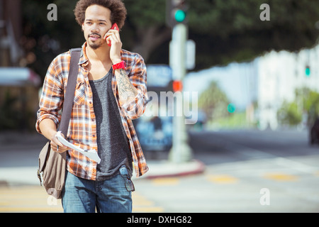Man talking on cell phone in urban crosswalk - Stock Photo