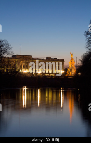 Buckingham Palace and Victoria Memorial reflected in lake in St James's Park at night twilight dusk London England - Stock Photo