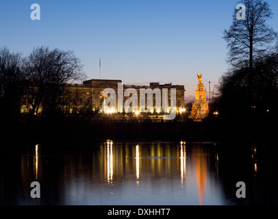 Buckingham Palace and Victoria Memorial reflected in lake in St James's Park at night London England UK - Stock Photo