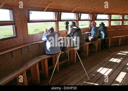 Birdwatchers in hide at Minsmere RSPB (Royal Society for the Protection of Birds) bird reserve, Suffolk, England - Stock Photo
