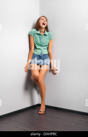 screaming woman stand in the corner of the room - Stock Photo