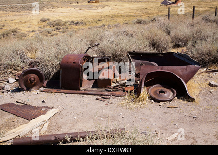 A dilapidated, rusting old car sets in the abandoned silver mining ghost town of Bodie, California - Stock Photo