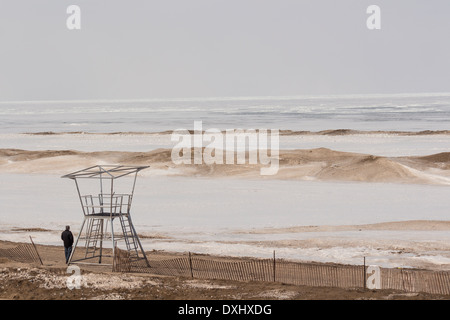 Man standing next to empty life guard stand on beach at Grand Bend, Ontario on Lake Huron, which is totally frozen. - Stock Photo