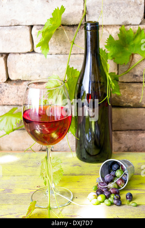 Bottle and glass of red wine next to the grape berries in a bucket - Stock Photo
