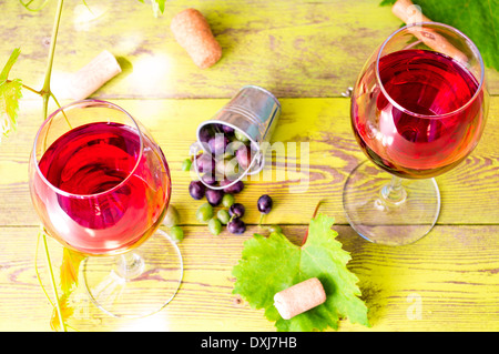 Two glasses of red wine next to the grapes in a bucket - Stock Photo