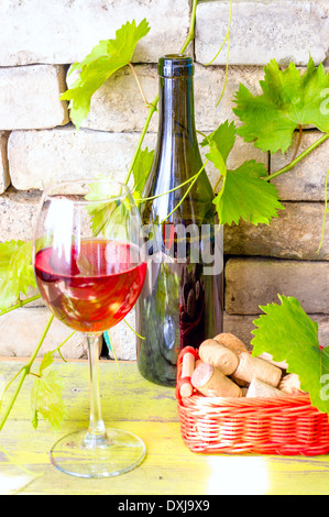 Bottle of red wine and a glass of wine next to a basket of wine corks. - Stock Photo