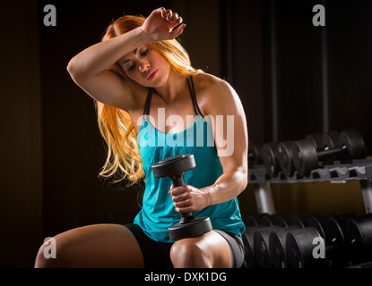 Caucasian woman wiping sweat from forehead in gym