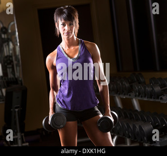 Portrait of confident Caucasian woman holding dumbbells in gym - Stock Photo