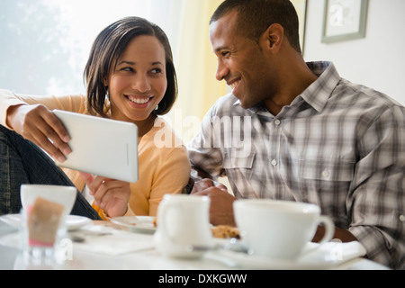 Happy couple drinking coffee and using digital tablet - Stock Photo