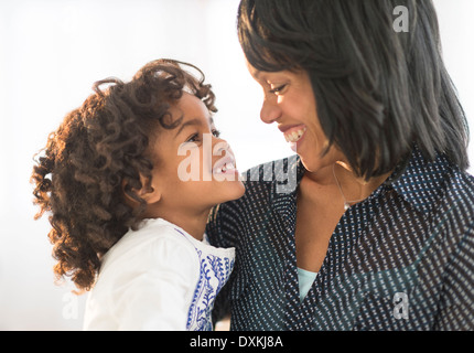 African American mother and daughter hugging and smiling - Stock Photo