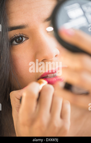 Close up of Hispanic woman applying lipstick in compact mirror - Stock Photo