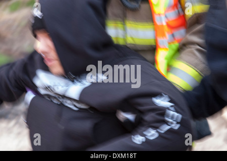 A victim being carried quickly from a shooting situation by a firefighter and police officer. Blur is intentional - Stock Photo