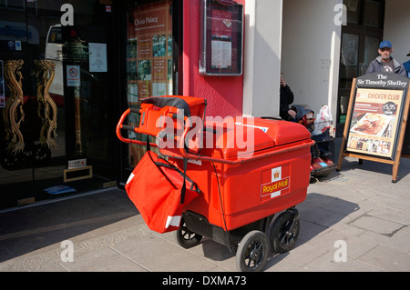 A postman's high capacity trolley containing letters & parcels for delivery now replacing the old fashioned bicycle - Stock Photo