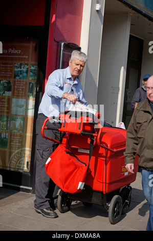 Postman on his round delivering letters & parcels using a 'high capacity' trolley (replacing the old fashioned bicycle) - Stock Photo