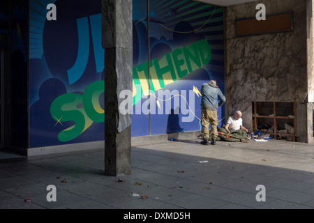 Two homeless people in a quiet corner close to a high street. - Stock Photo