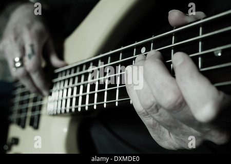 Guitar player with hand on fretboard and tattooed fingers plucking strings - Stock Photo