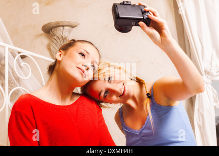 Two girls doing themselves photo in a bedroom - Stock Photo