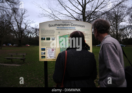 Hampshire England Southampton Common Man And Woman Looking At Cowherds Entrance Sign Site Of Special Scientific - Stock Photo