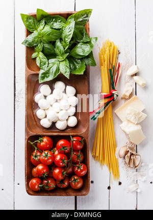 Italian flag colors with Green basil, white mozzarella, red tomatoes, parmesan and spaghetti - Stock Photo