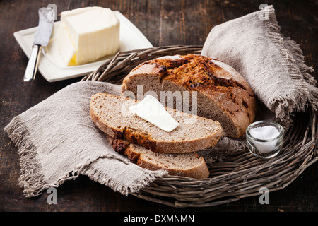Rye sliced bread and butter on wooden table - Stock Photo