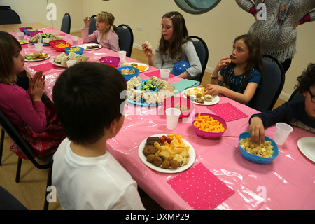 8 Year Old Girl's Birthday Party Children At The Table Eating Food Dorset England - Stock Photo
