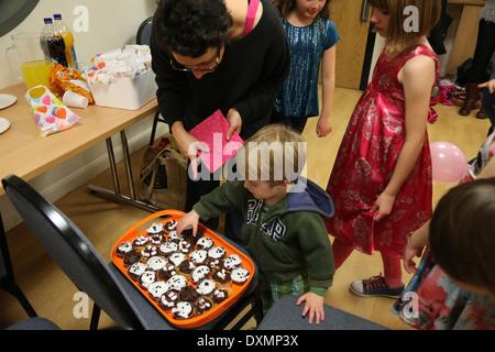 8 Year Old Girl's Birthday Party Boy Choosing Homemade Cupcake Dorset England - Stock Photo