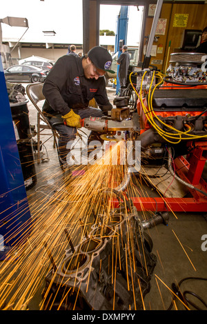 Sparks fly as a teenage boy grinds a metal engine fitting in auto shop class in San Clemente, CA. - Stock Photo