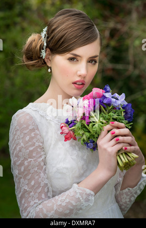 Young bride holds a wildflowers bouquet, - Stock Photo