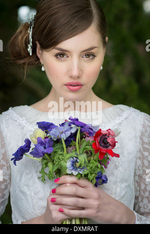 Young bride with wild flowers bouquet - Stock Photo