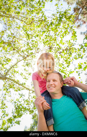 Cute Young Girl Rides Piggyback On Her Dads Shoulders Outside at the Park. - Stock Photo