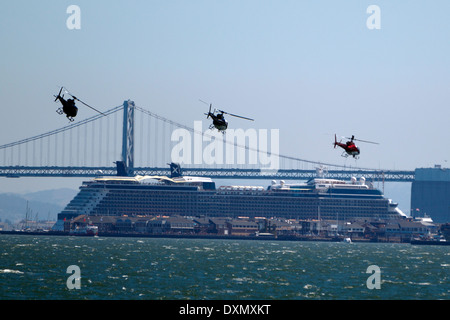 Three helicopters flying in formation in front of a cruise ship and the Bay Bridge, San Francisco Bay, San Francisco, - Stock Photo