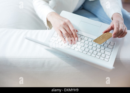 Hands of female sitting at the laptop with a credit card - Stock Photo